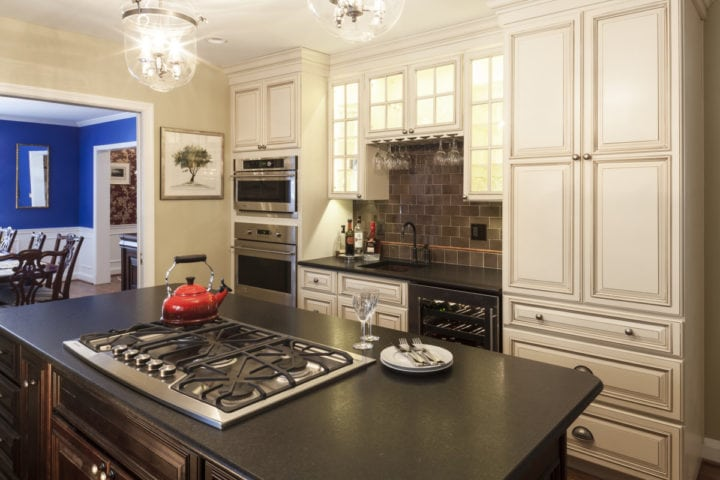 traditional stained wood island with black leather granite top with cook top