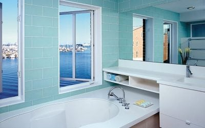 bathroom with white tub and windows open to bay view