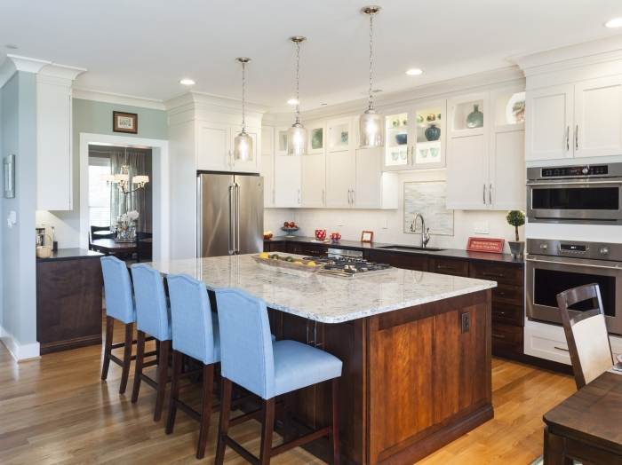 two tone white upper kitchen cabinets and stained wood lower with white granite top island and leather black granite perimeter counter top