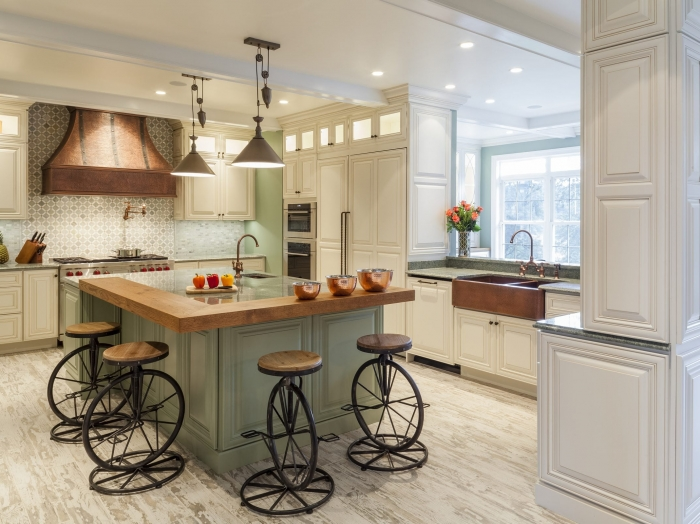 kitchen with cream cabinets with green engineered stone top and green painted island with wood counter top and white distressed wood floor