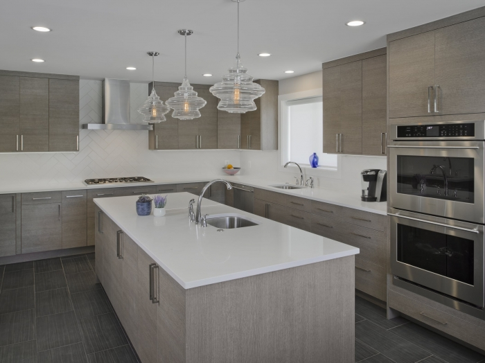 modern kitchen with gray cabinets, white counter tops and slate tile