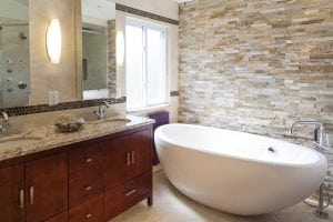 Bathroom with white tub and textured stone walls