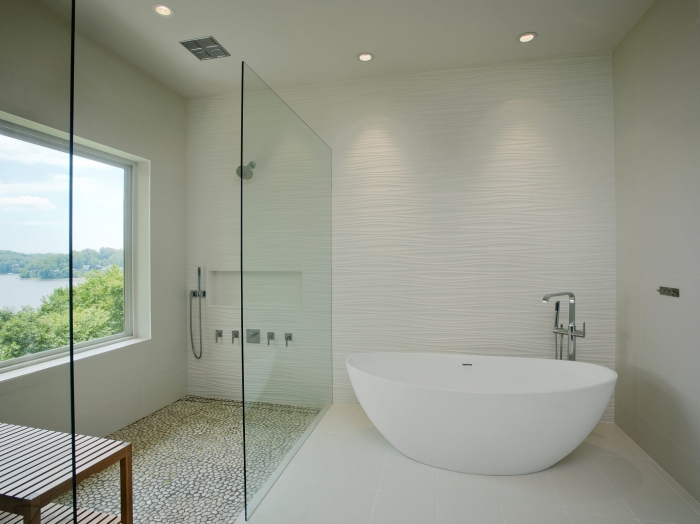 Waterfront modern master bathroom with walk in shower & freestanding tub, floor to ceiling tile walls