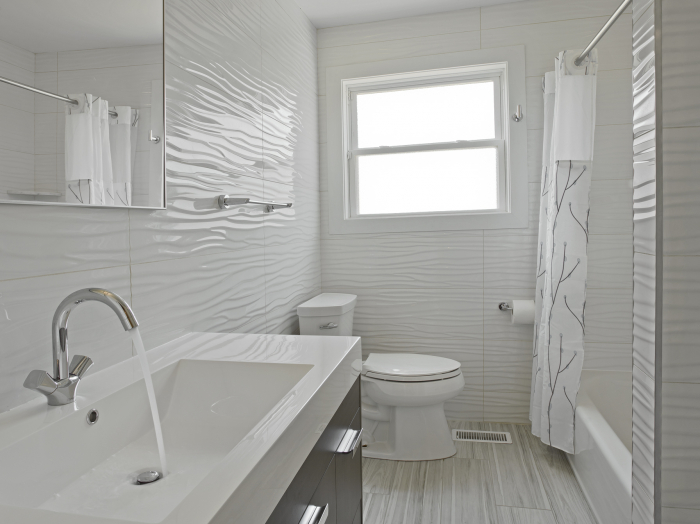 modern white bathroom with stained wood vanity and rectangular sink, white floor to ceiling wave tile