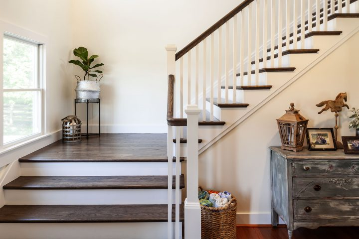 traditional staircase with dark wood landing and white wood balusters