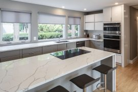 white quartz countertop and floor to ceiling white modern kitchen cabinets